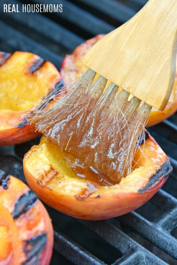 basting brush coating peach halves on the grill