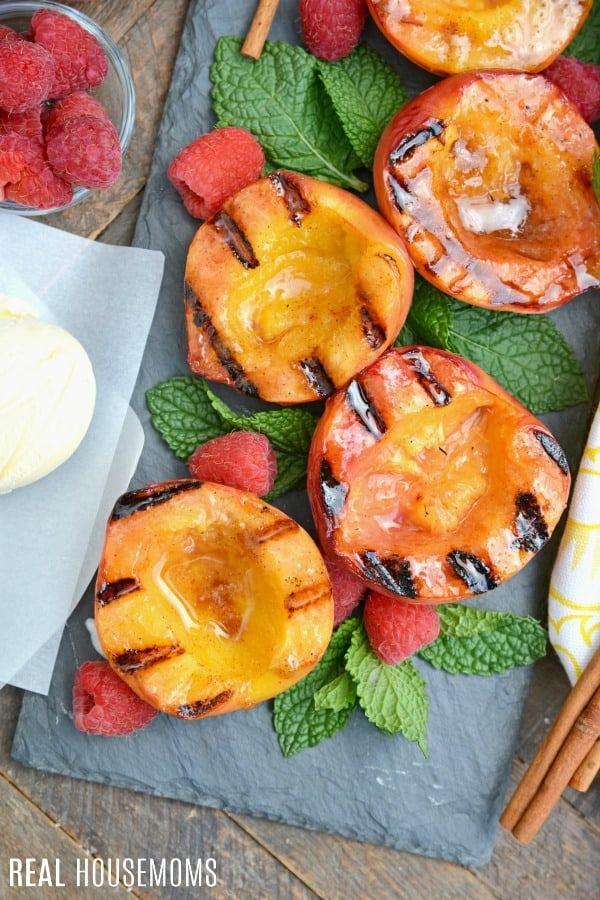 overhead picture of grilled peaches with mint and raspberries