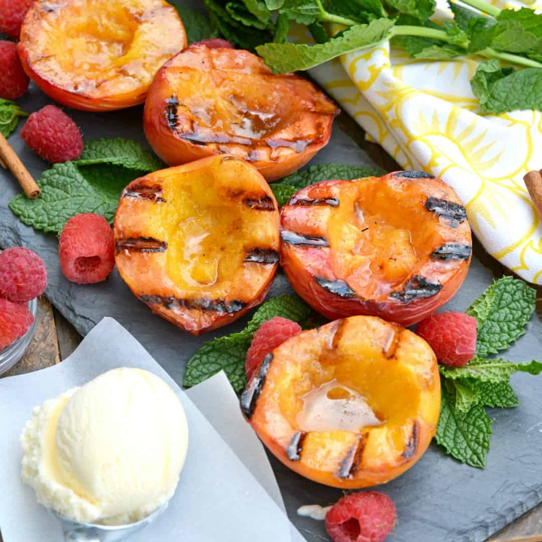 Summer desserts don't get better than Grilled Peaches basted with cinnamon, brown sugar & butter. Serve them with vanilla ice cream and raspberries for the ultimate dessert recipe!