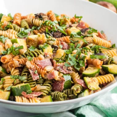square image of grilled vegetable pasta salad in a serving bowl