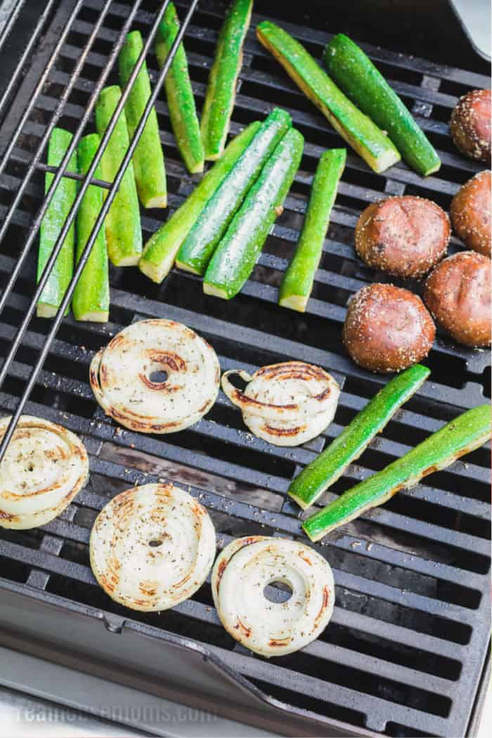 onion slices, mushrooms, and zucchini on a grill
