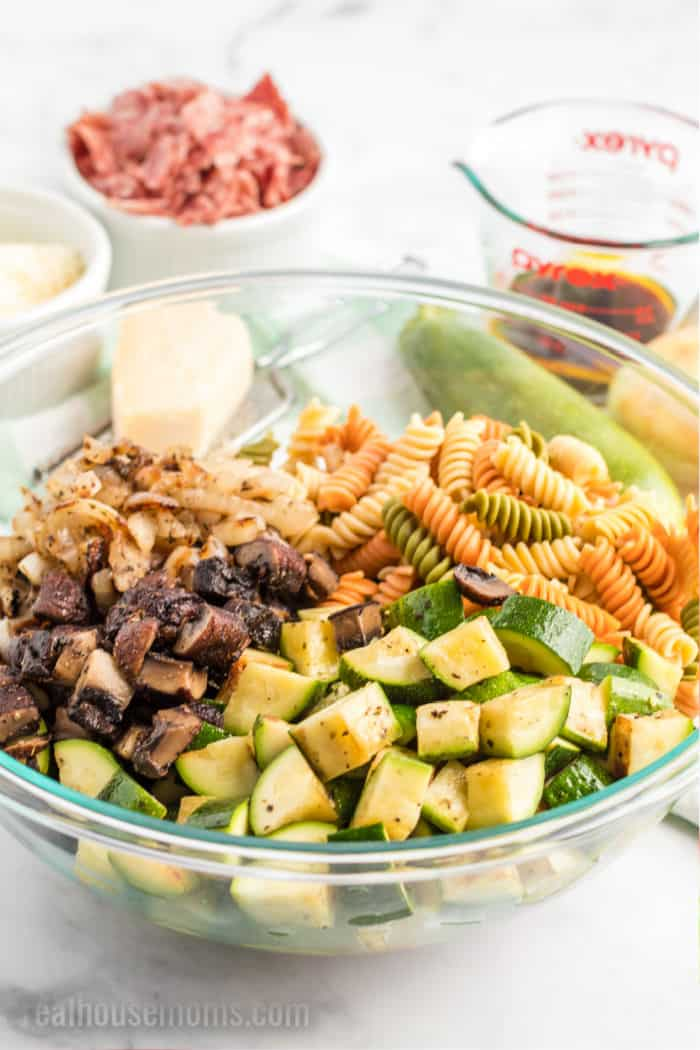 chopped grilled vegetables and cooked rotini pasta in a mixing bowl