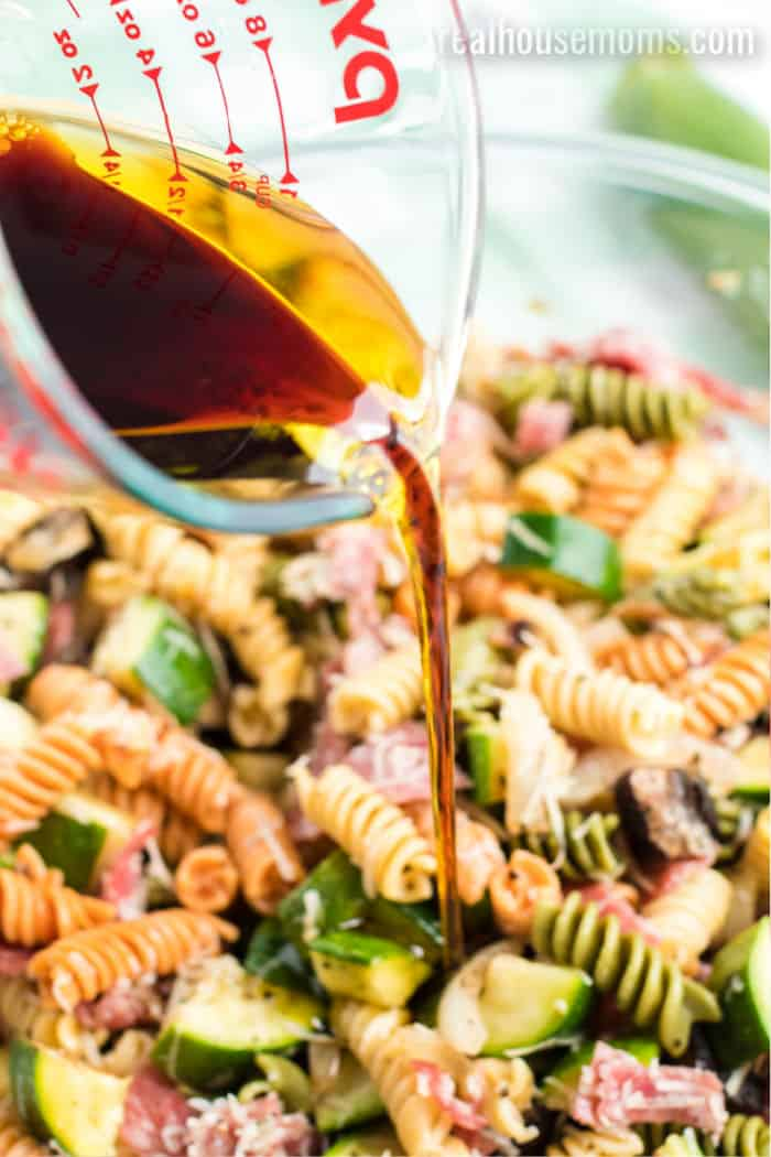 olive oil and balsamic vinegar mixture being poured onto pasta salad