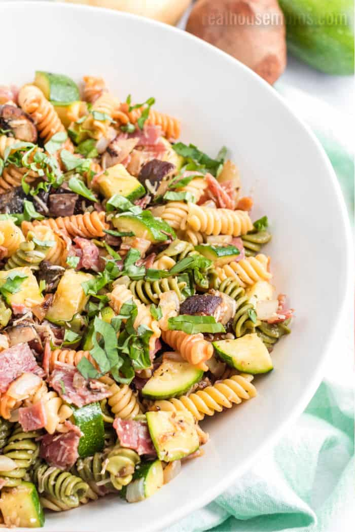 vegetable pasta salad in a serving bowl topped with basil