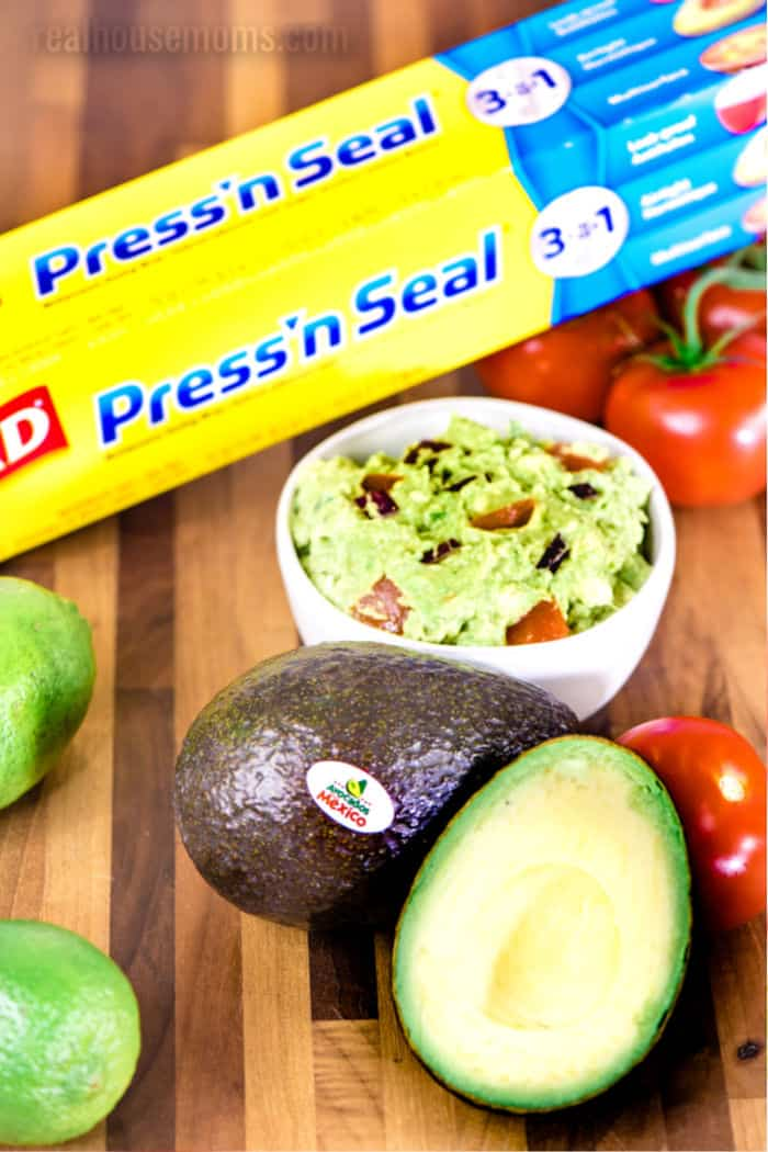 avocado cut in half next to a bowl of guacamole and a box of glad press 'n seal