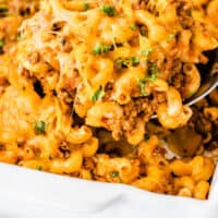 spoonful of hamburger casserole over the baking dish with recipe name at the bottom