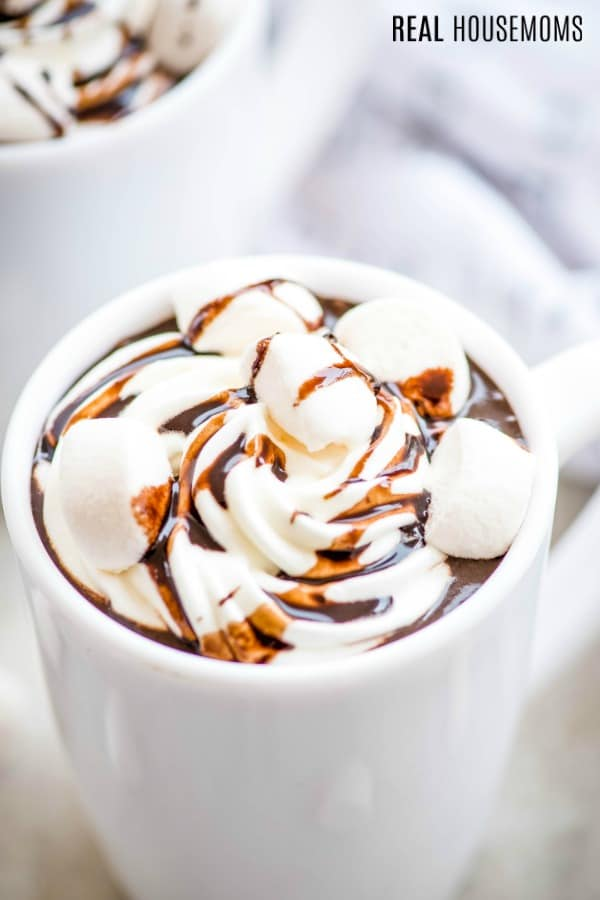 close up of a mug of homemade hot chocolate with marshmallows, whipped cream, and chocolate sauce