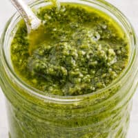 square close up image of homemade pesto sauce in a jar with a spoon