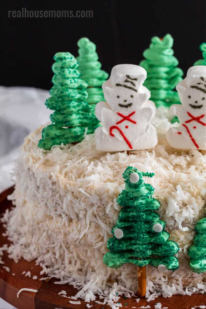 snowman peeps and candy pretzel tress on a coconut covered cake