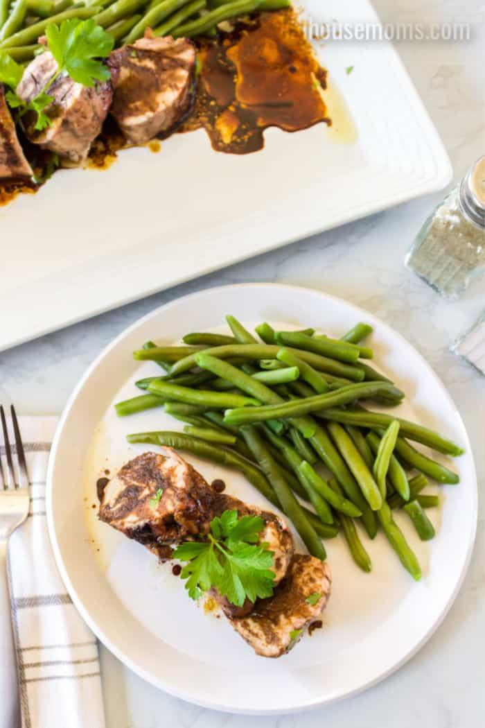 pork tenderloin on a plate with green beans