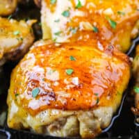 honey garlic chicken thigh s in a cast iron skillet with recipe name at bottom