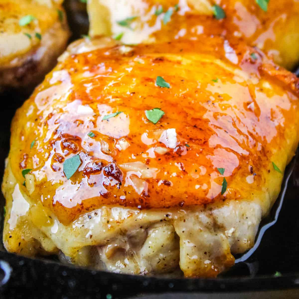 square image of a hony garlic chicken thigh in a skillet