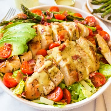 honey mustard chicken salad in a bowl with avocado, asparagus, and tomatoes