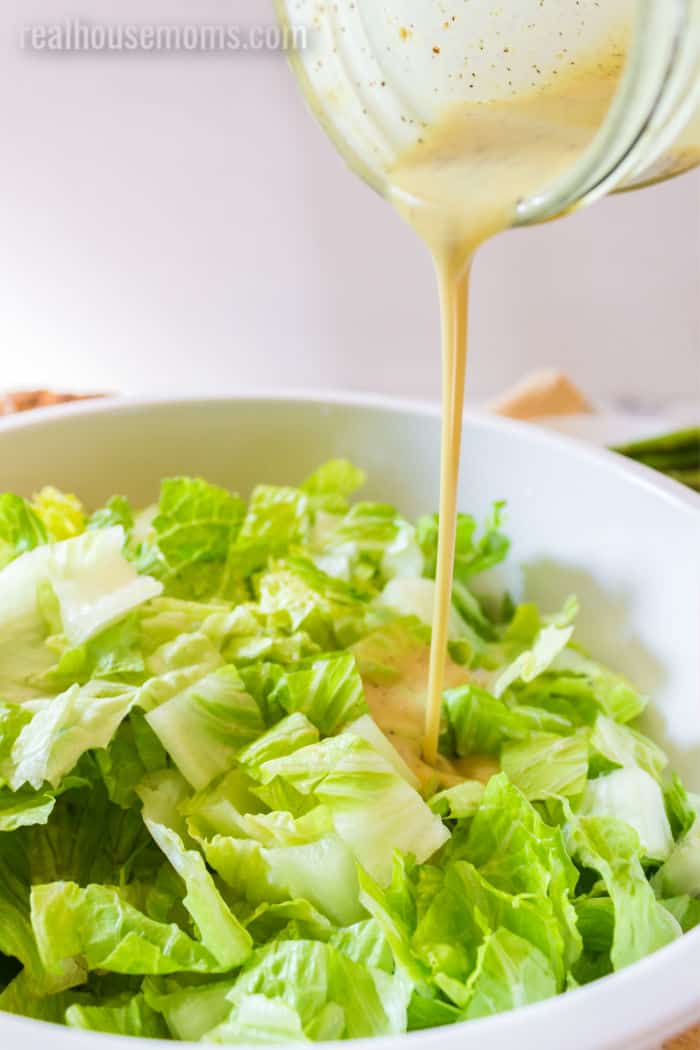 honey mustard dressing being poured over lettuce in a serving bowl