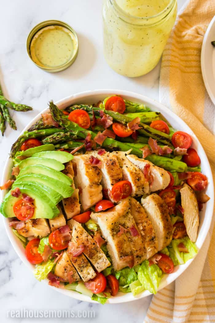 lettuce topped with sliced grilled chicken, cherry tomatoes, cooked asparagus, sliced avocado, and bacon
