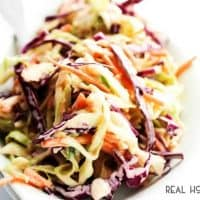 This HONEY SRIRACHA COLESLAW is made with 2 kinds of cabbage and a creamy honey dressing with a kick. Coleslaw has never tasted so good.