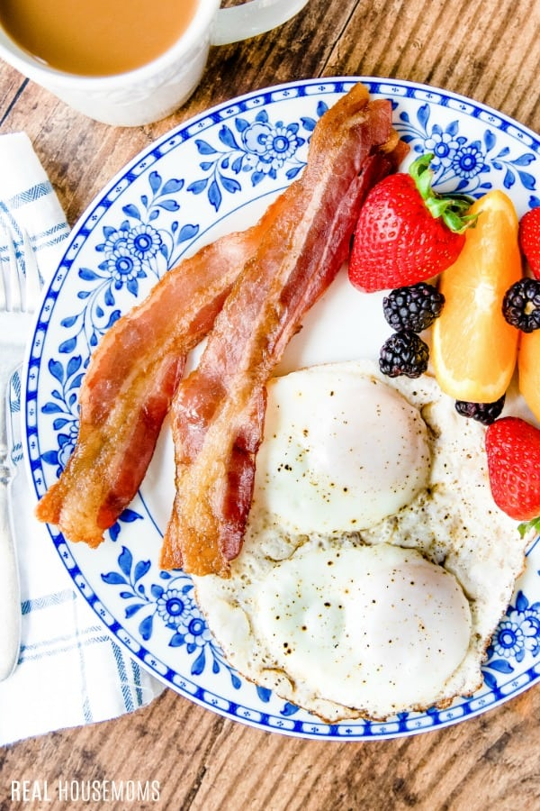 bacon, eggs, and fruit on a plate