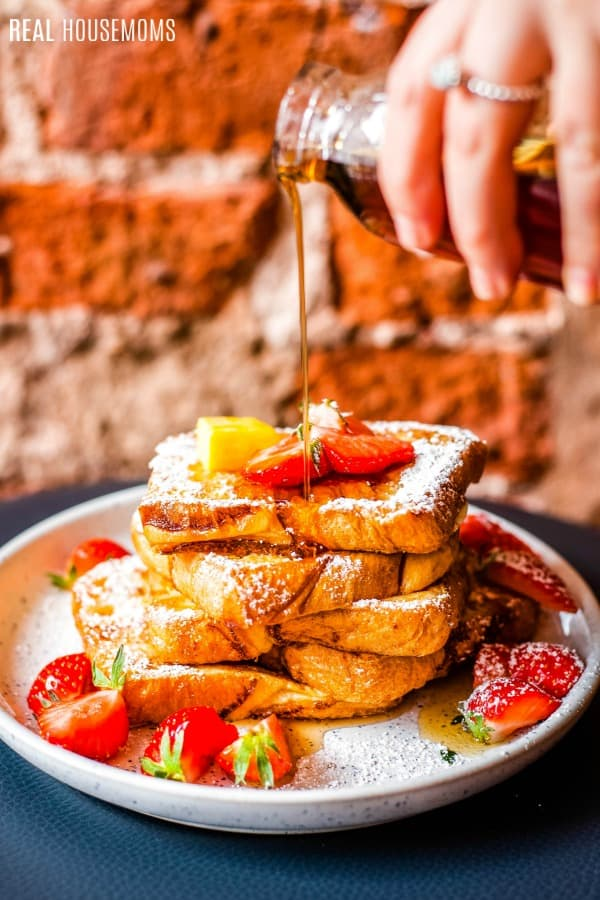 syrup being poured onto a plate of french toast