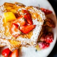 This easy recipe will show you How to Make French Toast your whole family will love! Soft brioche bread dipped in a cinnamon egg mix & fried until golden!