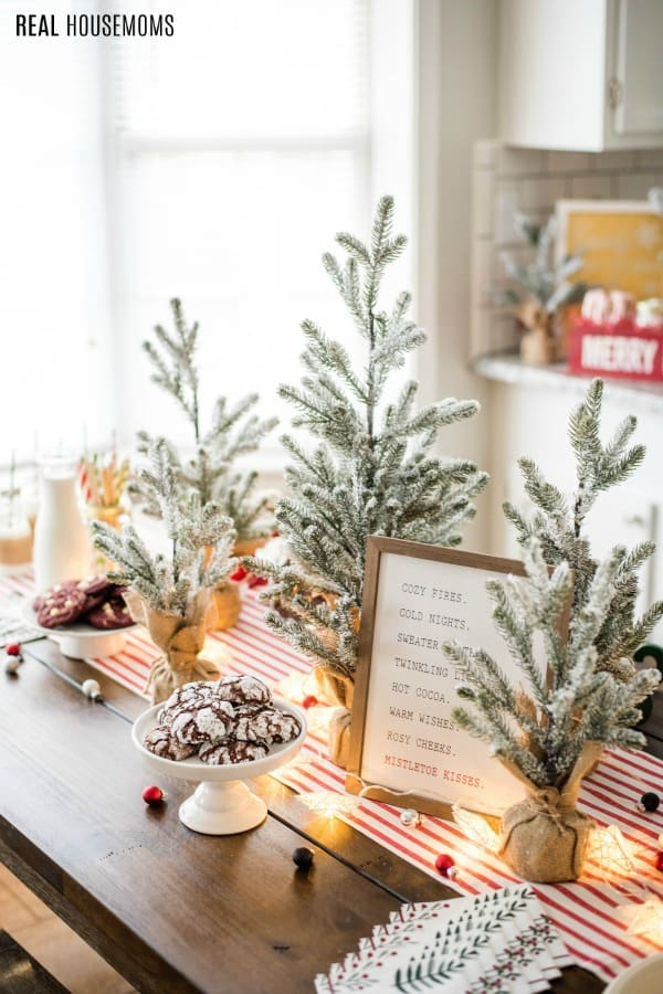 table decorated for a cookie exchange holiday party with trees and cookies on cake stands