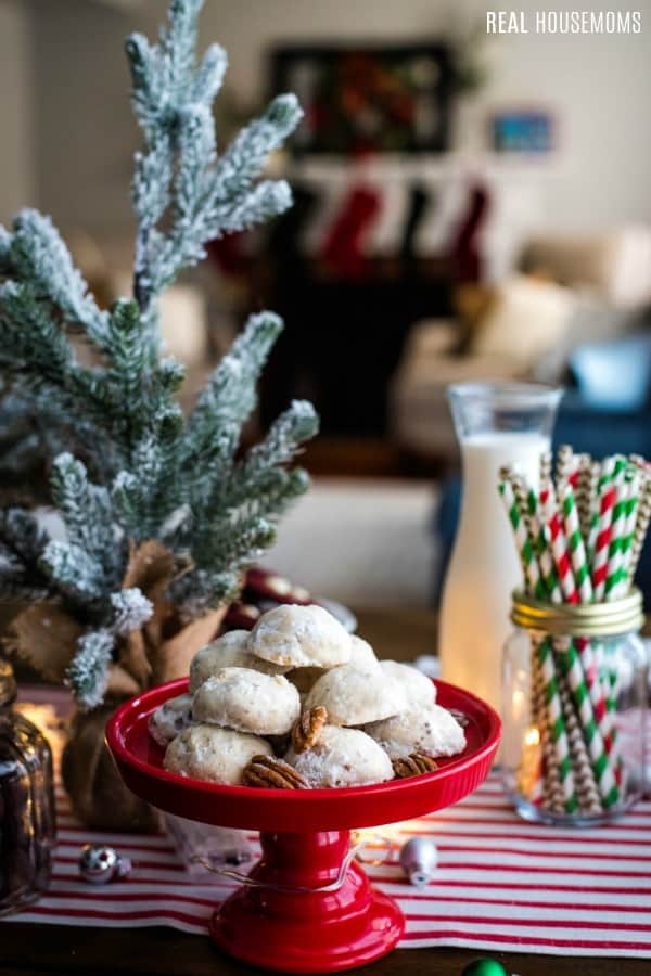 cookies on a cake stand next to holiday party decor