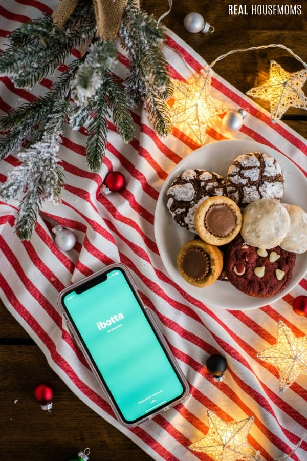 phone with Ibotta app open next to plate of cookies to prep for a holiday party