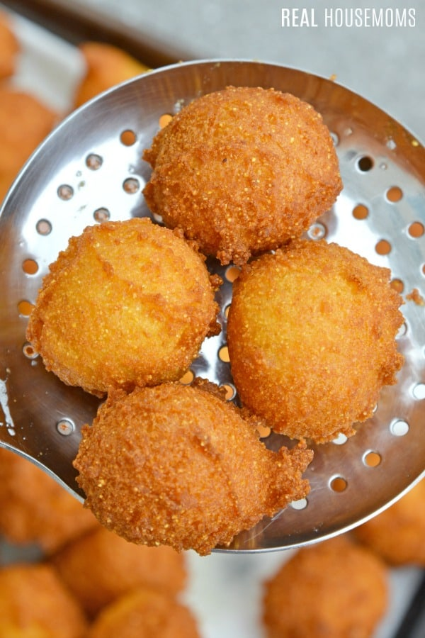 golden brown hush puppies being taken out of the pot just after frying