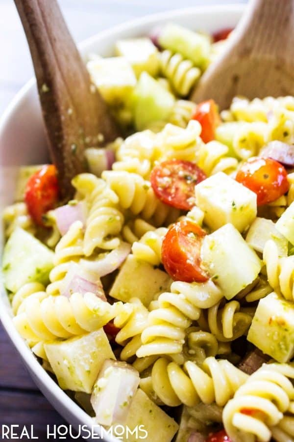 Italian Pesto Pasta Salad in a serving bowl with two wooden spoons for portioning