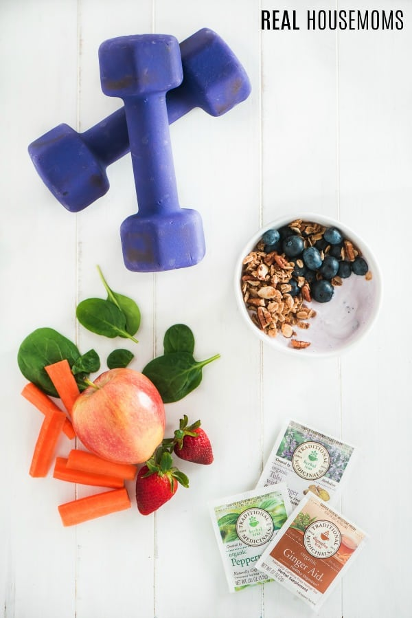 dumbells, fruit & vegetables, yogurt, bowl, and tea packets