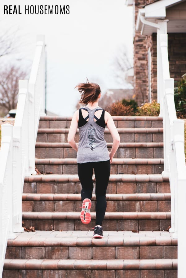 woman in workout clothes running up brick stairs