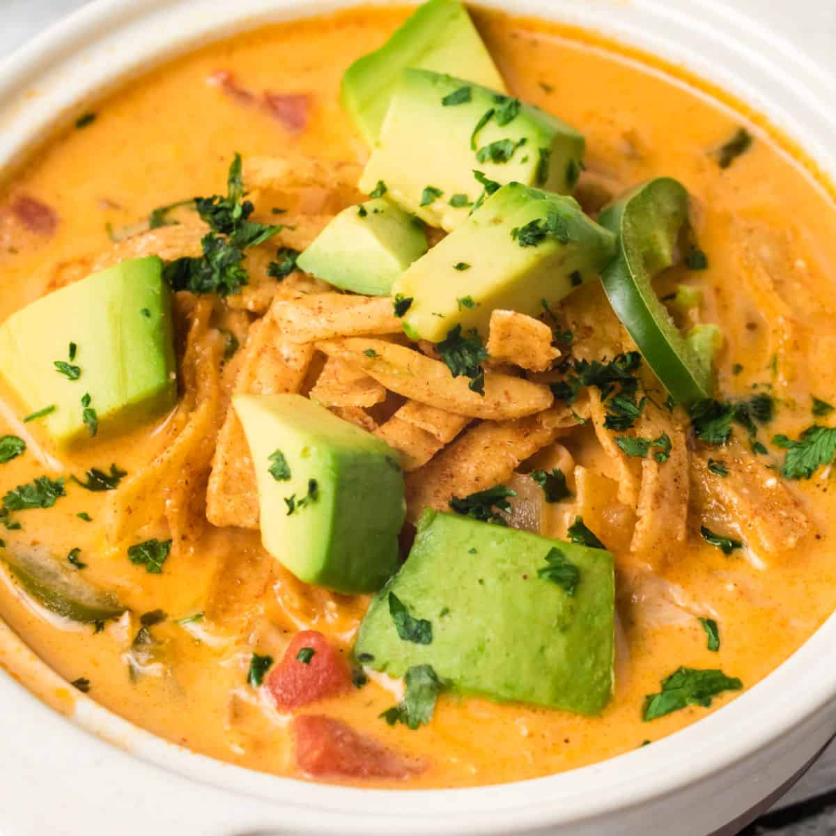 square image of chicken tortilla soup in a bowl with tortilla strips, avocado, and jalapeno
