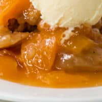 close up of instant pot peach cobbler on a plate with a scoop of vanilla ice cream with recipe name at bottom