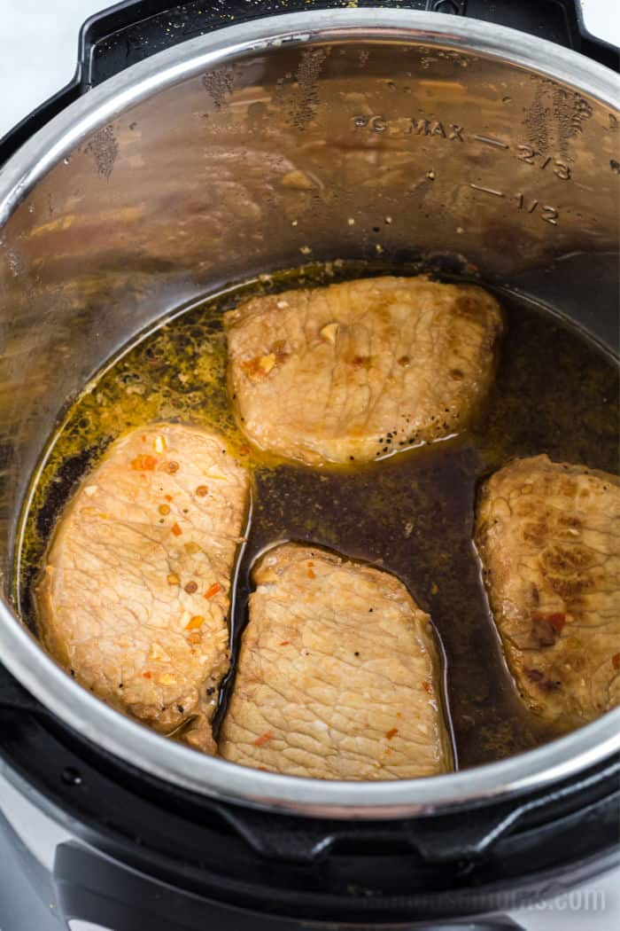 pork chops in liquid in an instant pot with the lid off