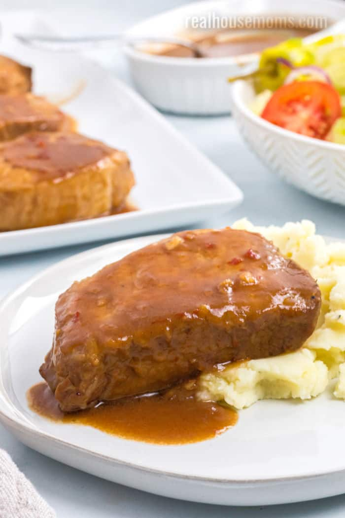 pork chop topped with sauce on a plate with mashed potatoes