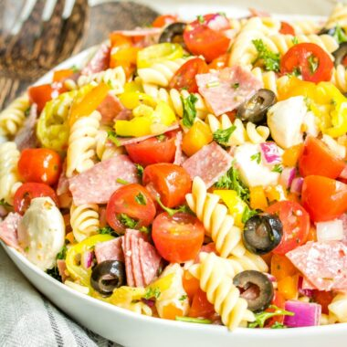 Italian Pasta Salad is a tasty cold pasta salad with mozzarella, salami, peppers, and olives mixed in a tangy Italian dressing. The perfect potluck dish!
