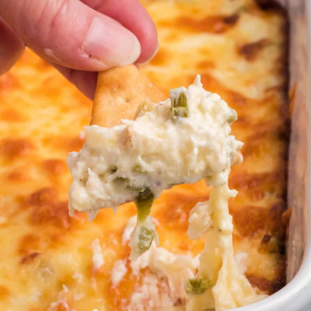 square image of a pita chip dipped into jalapeno crab dip