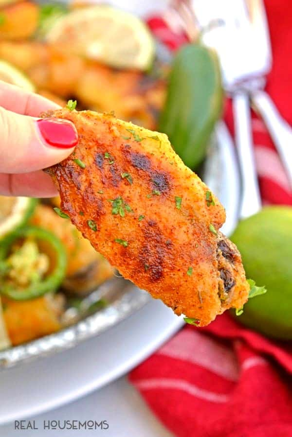 Fingers picking up a crispy Jalapeno Lime Chicken Wing