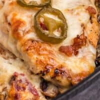 jalapeno popper stuffed chicken breast in a cast iron skillet with recipe name at bottom