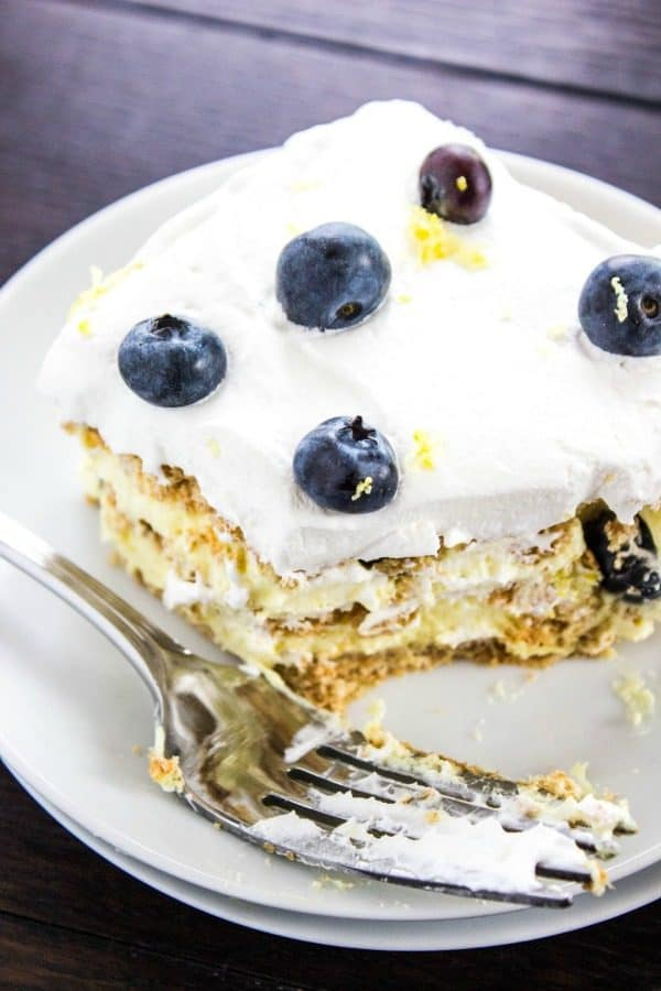 Slice of Lemon Blueberry Icebox Cake with a bite missing and fork resting on the plate.