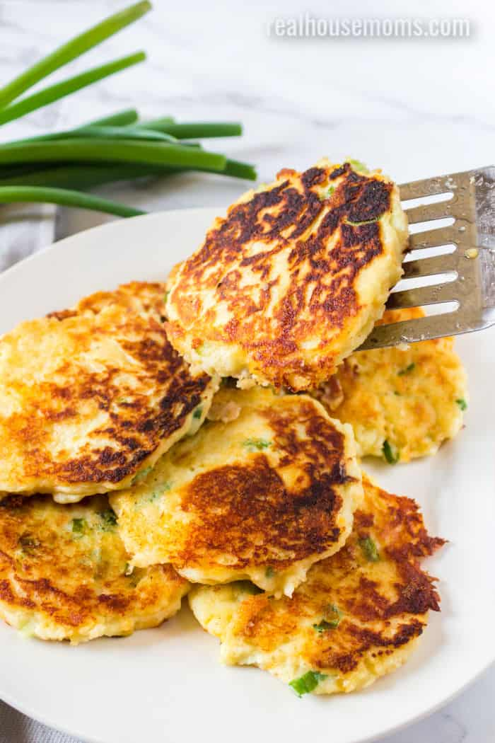 spatula putting a potato pancake onto plate