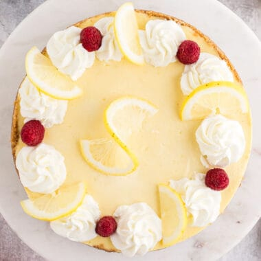 sqiare image of lemon cheesecake topped with whipped cream dollops, lemon slices, and fresh raspberries