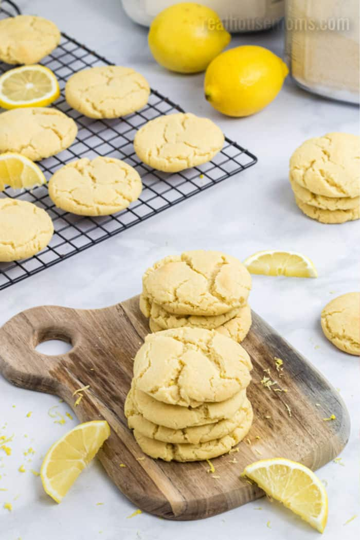 lemon sugar cookies stacked up and on a cooling rack with fresh lemons