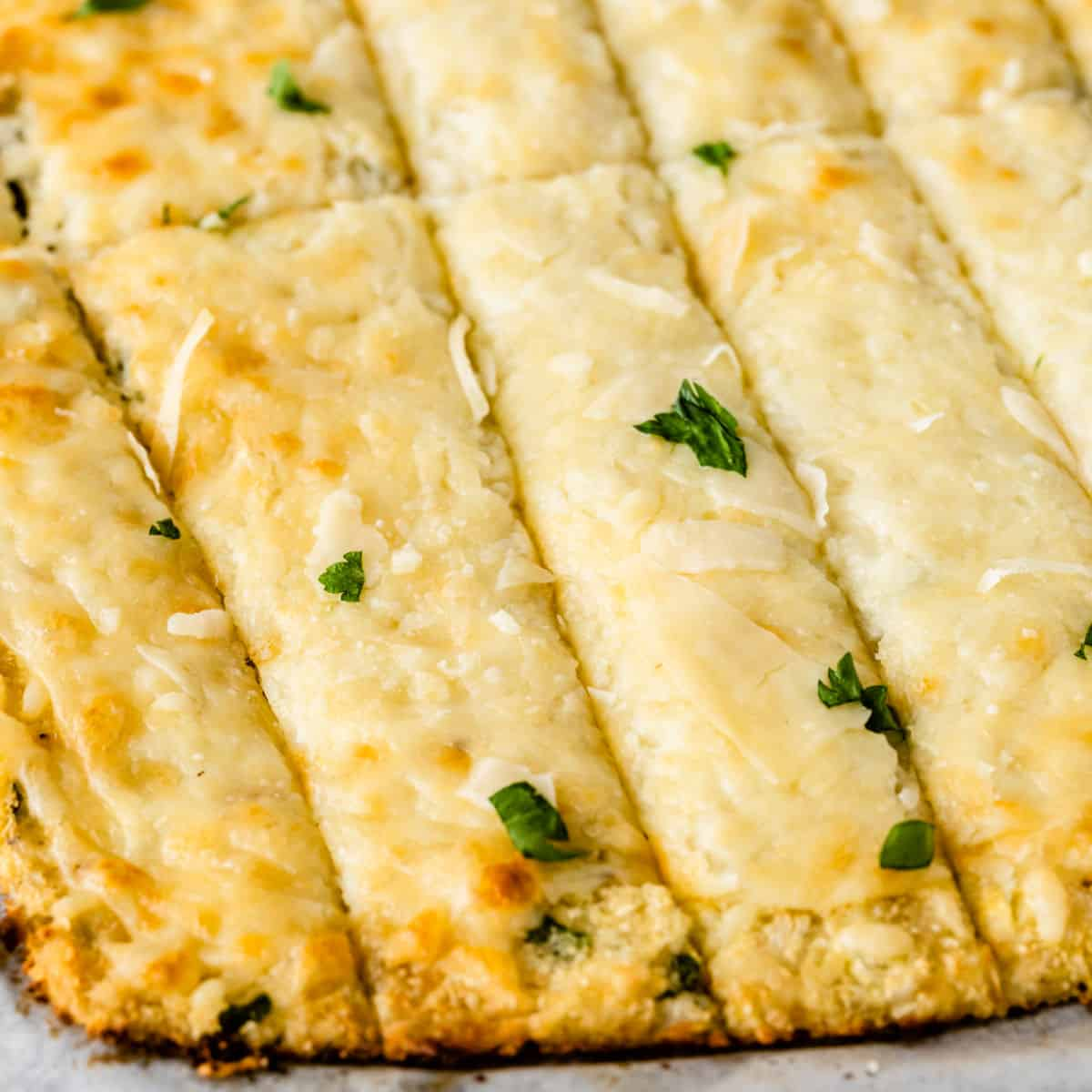 square image of low carb cauliflower breadsticks cut into strips