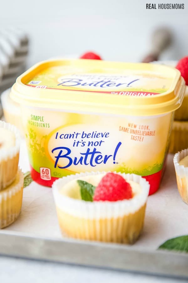 Tub of I Can't Believe It's Not Butter on a baking sheet surrounded by low carb cheesecake bites