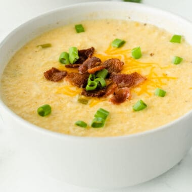square image of cauliflower chowder in a white bowl topped with cheese, bacon, and green onion