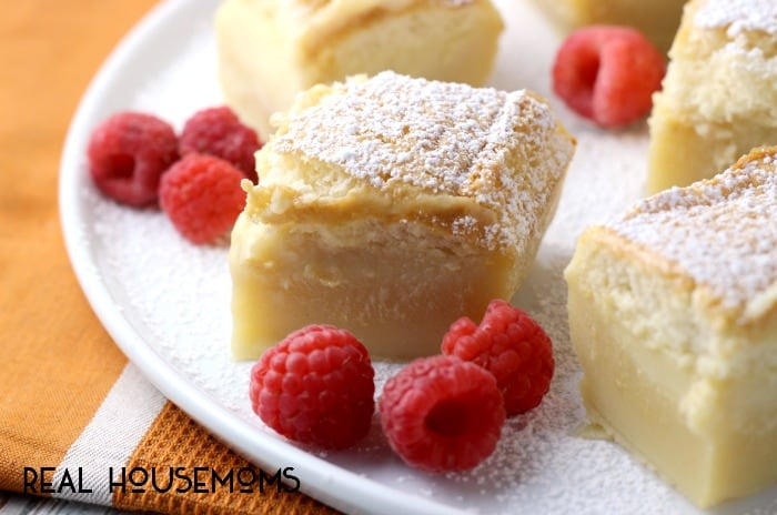 Magic Custard Cake slices on a plate surrounded by raspberries