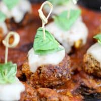 Meatball Parmesan Bites are the perfect appetizer for your next get together.  Tender meatballs, infused with garlic, breadcrumbs, and parmesan are smothered in red sauce and topped with mozzarella & basil for a burst of Italian flavor!