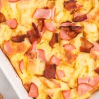 meaty eggs benedict casserole in a baking dish with recipe name at bottom