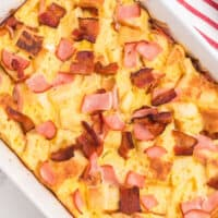 square image of meaty eggs benedict casserole in a baking dish
