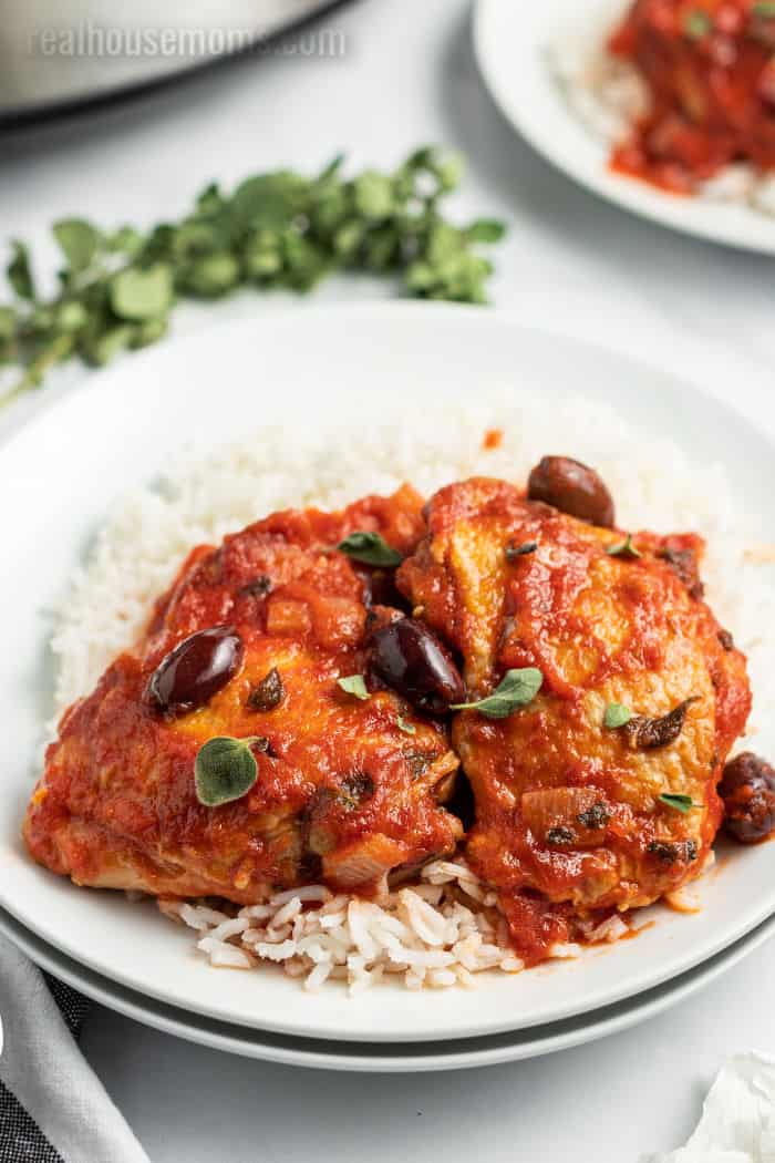 Mediterranean crock pot chciken thighs on a plate with rice and extra tomato sauce